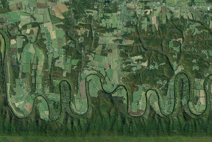 Плавная лента реки Шенандоа, протекающей среди густой зелени.