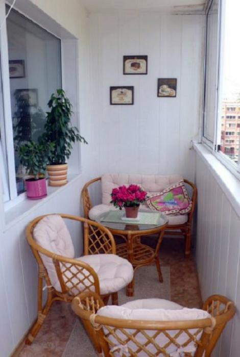 Простенький балкон с плетеной мебелью.