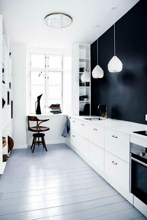 Узкая кухня с черной стеной.