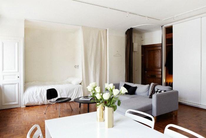 Светлая комната с кроватью в нише и серым диванчиком.