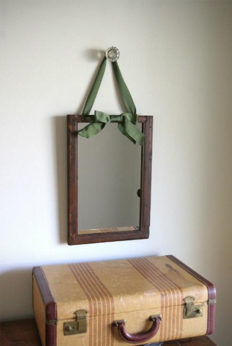 Рама из темного дерева, украшенная атласной лентой.
