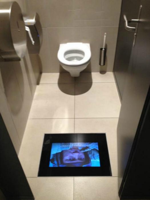 Телевизор вмонтированный в пол туалетной комнаты.