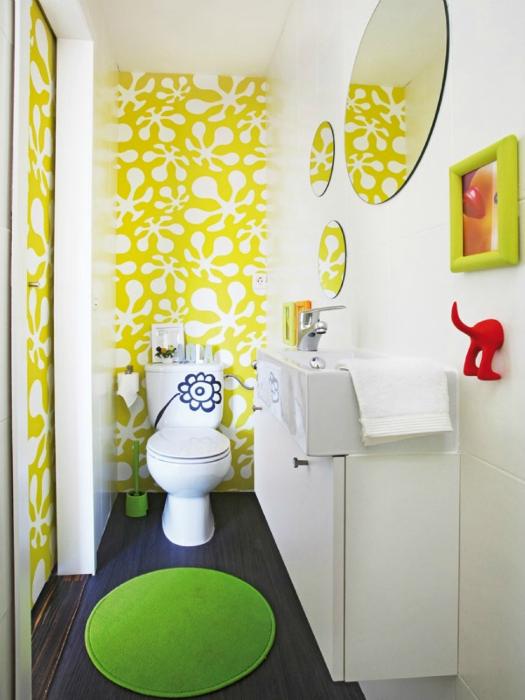 Узкий санузел с желтыми узорами на стене.