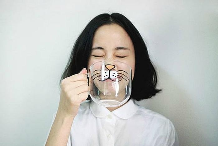 Большая чашка, украшенная кошачьей мордочкой.