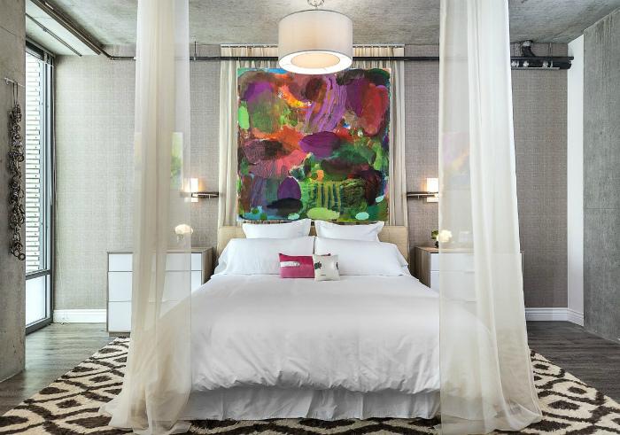 Светлая спальня с красочной картиной в изголовье кровати.