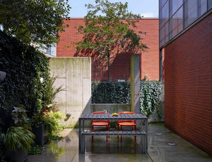 Простая мебель и вьющаяся стена на заднем дворе.