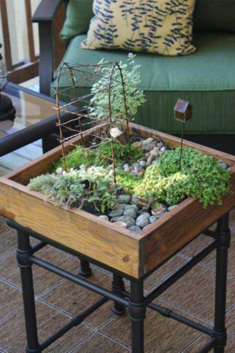 Композиция из небольших растений, камешков, фигурок и подставок для цветов в нише старого кофейного столика.