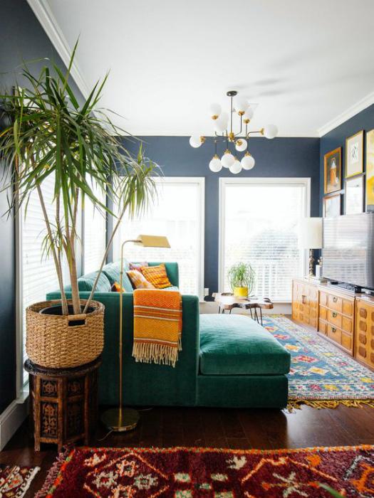 Уютная гостиная с эффектным зеленым диваном.