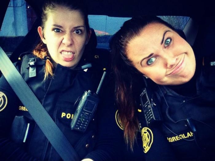 Девушки-полицейские корчат смешные рожицы в служебной машине.