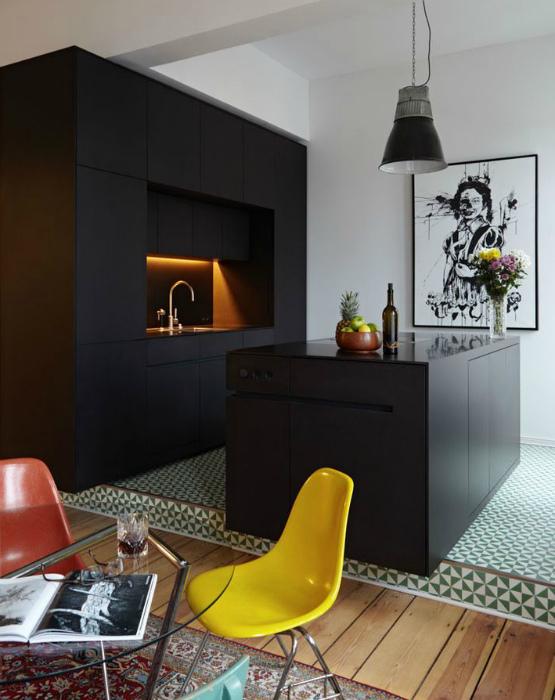 Небольшая современная кухня с черной мебелью.