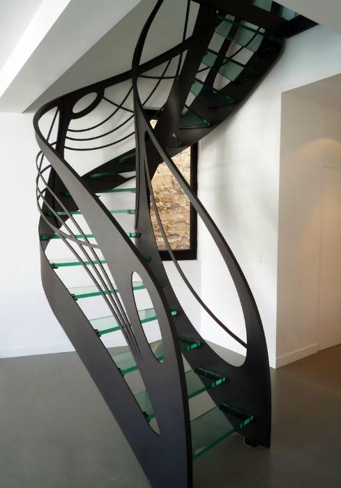 Лестница со скульптурными перилами и стеклянными ступенями.
