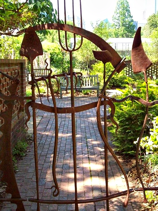 Небольшая металлическая калитка с элементами садового инструмента.