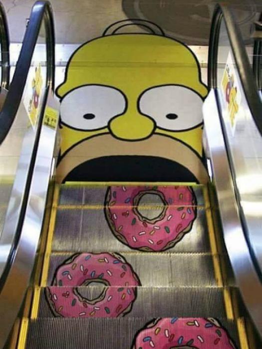 На ступеньках эскалатора изображены пончики, которые движутся прямо в рот нарисованному Гомеру Симпсону.