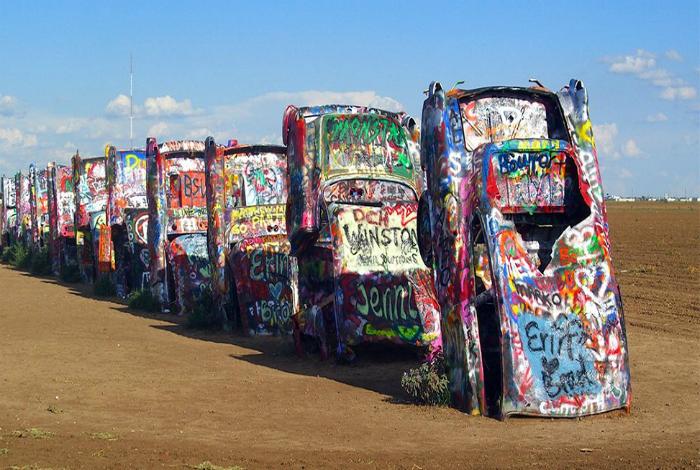 Десять автомобилей на одинаковом расстоянии вкопанных в землю, на которых туристы оставляют свои послания.
