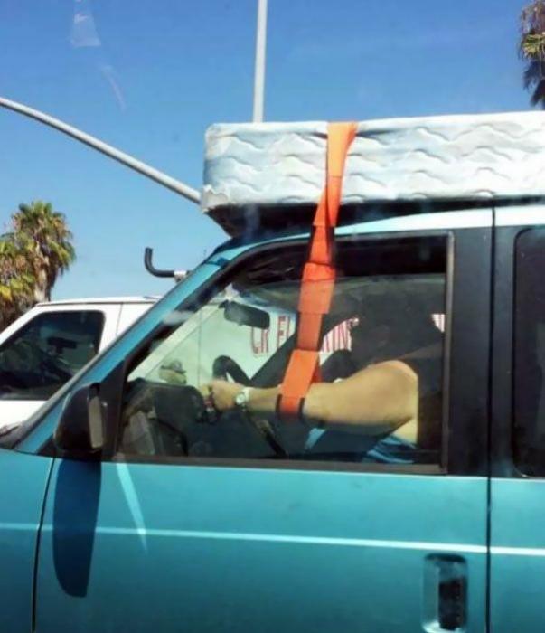Водитель страхует матрас на крыше.