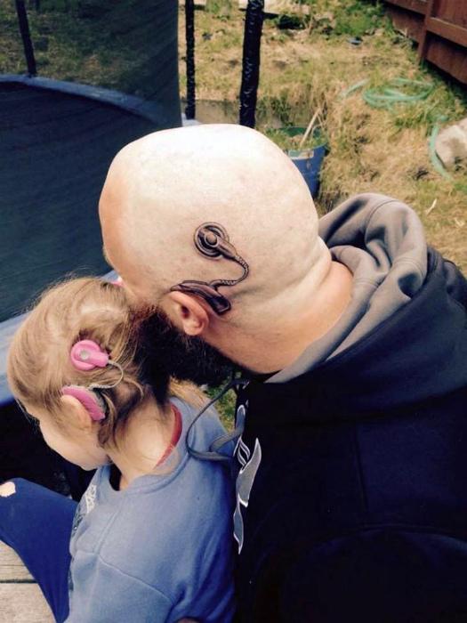 Тату с изображением слухового импланта.