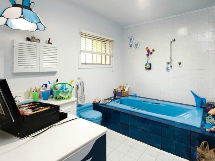 Светлая ванна с яркой сантехникой.
