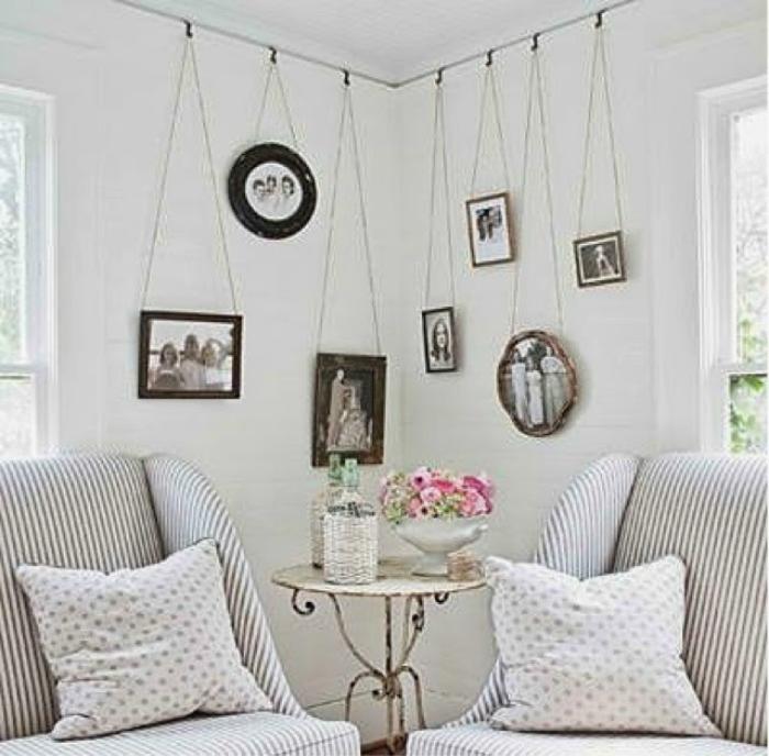 Фотографии в красивых рамках, прицепленные веревками к креплению под потолком станут отличным украшением гостиной.