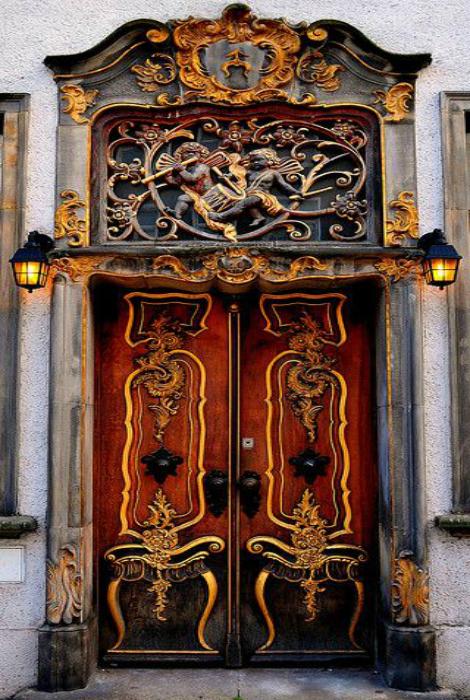 Массивная деревянная дверь, украшенная коваными элементами.