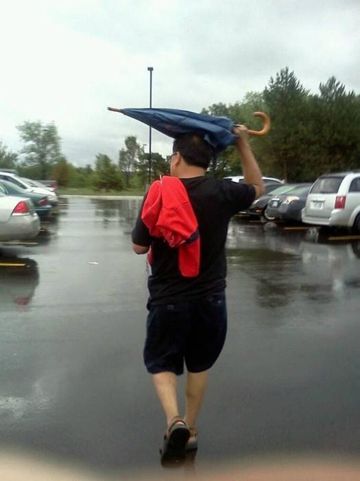 Мужчина, который не знаком со сложной конструкцией зонта.