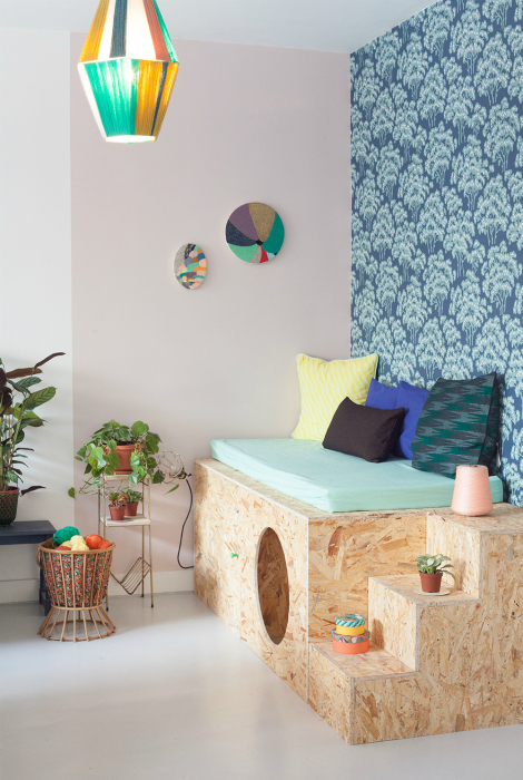 Комната с акцентной стеной и оригинальным диванчиком.