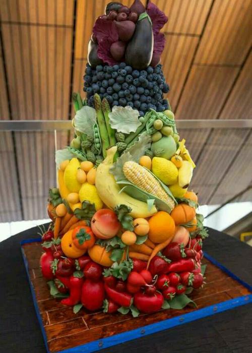 Огромный торт, украшенный сахарными овощами, фруктами и ягодами.