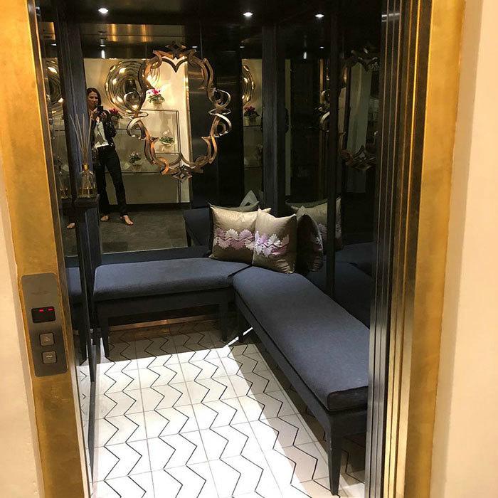 Лифт с зеркальной стеной и диванчиком.