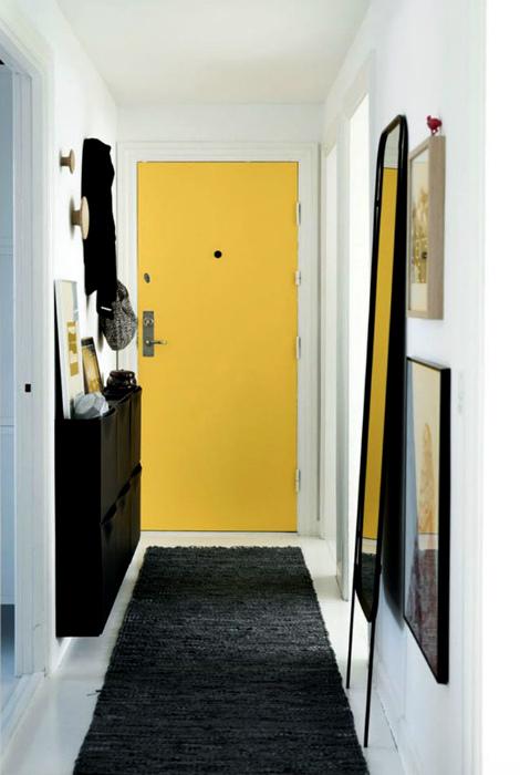 Прихожая со светлыми стенами и желтой дверью.