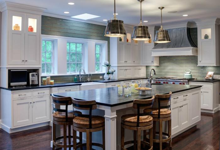 Функциональная и современна кухня с множеством рабочих поверхностей, мощной вытяжкой и большим обеденным столом в центре.