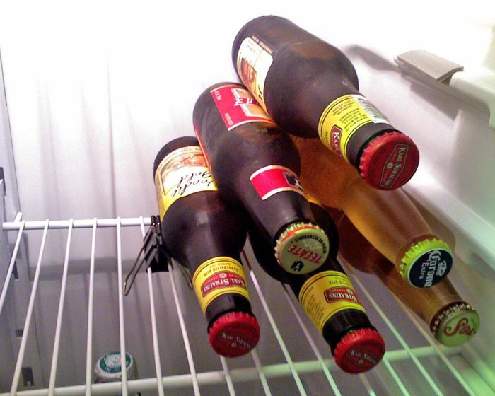Используйте канцелярский зажим, чтобы зафиксировать бутылки в холодильнике горизонтально.