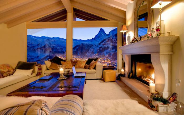 Светлая комната с белоснежными диванами и ковром, уютным камином и огромным окном.