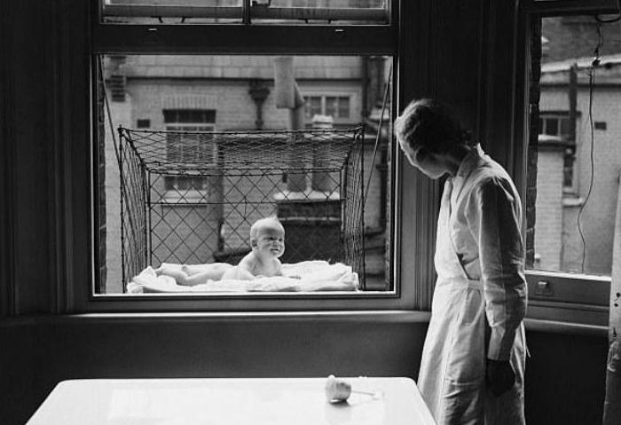 В такие конструкции помещали малышей и вывешивали за окно, чтобы ребенок дышал свежим воздухом. 1930 год.