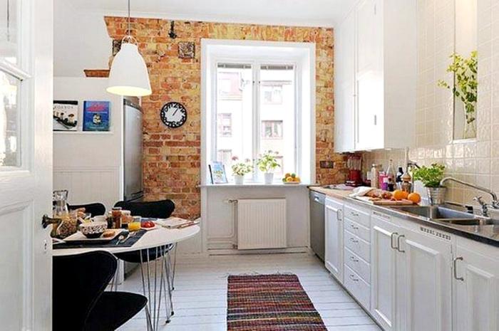 Светлая кухня с имитацией кирпичной кладки на одной из стен.