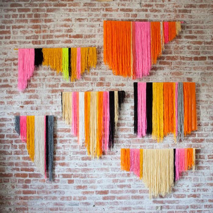 Яркие нитки, свисающие с деревянных пластин - оригинальное и простое украшение для стен.