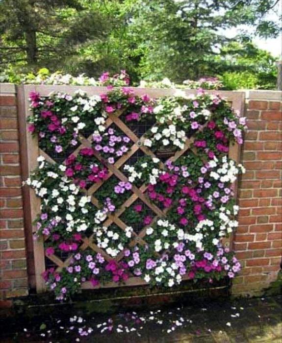 Фрагмент забора, украшенный цветами и штакетником. | Фото: Pinterest.
