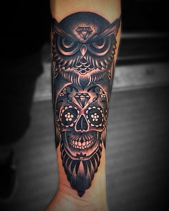 Темная татуировка с изображением совы и черепа.