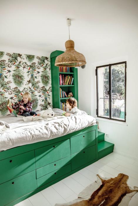 Спальня с флористическими обоями и зеленой кроватью.