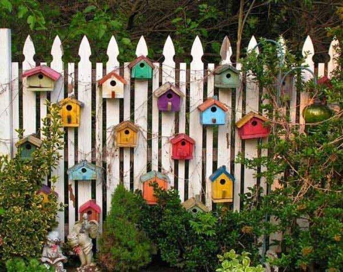 Забор, украшенный деревянными скворечниками.
