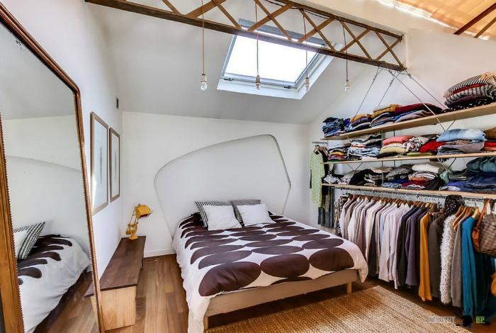 Спальня с открытым гардеробом и красивой кроватью.