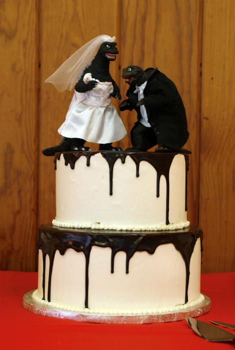 Свадебный торт, украшенный фигурками в виде Годзиллы и динозавра.