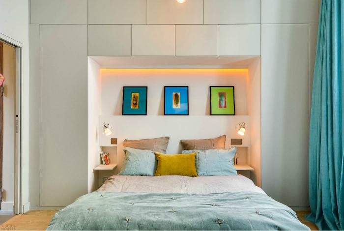 Спальня с большим стеллажом в изголовье.