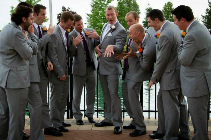 Мужчина хвастается своим обручальным кольцом перед друзьями, подражая своей новоиспеченной жене.
