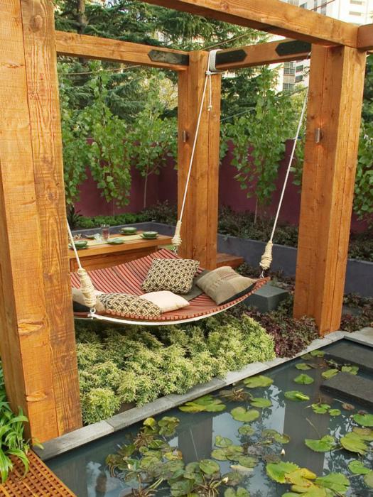 Место для отдыха со столом и тканевыми качелями.