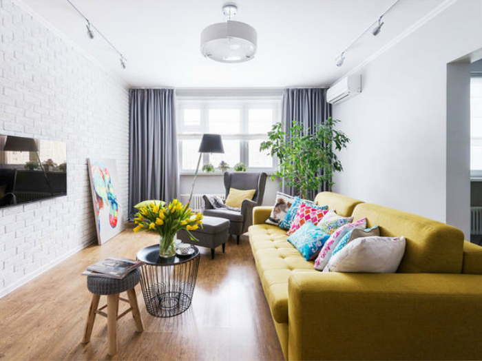 Светлая гостиная с ярким диваном.