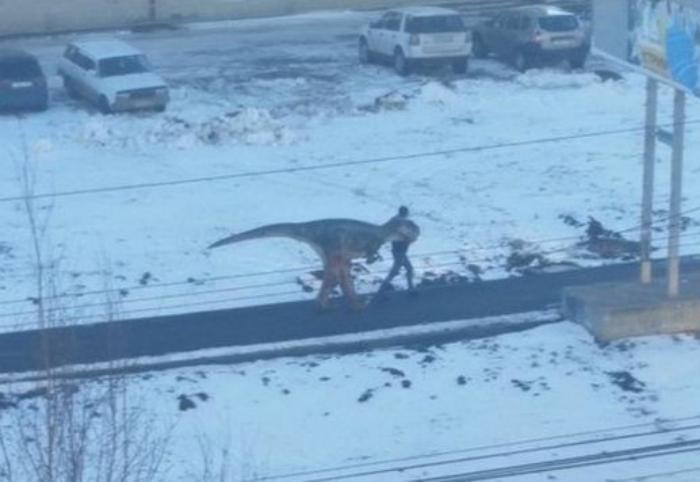 Человек выгуливает динозавра.