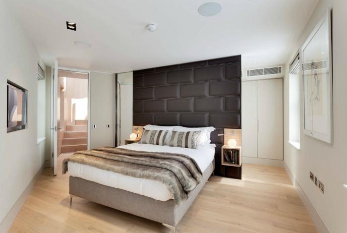Светлая спальня с акцентной стеной в изголовье кровати.