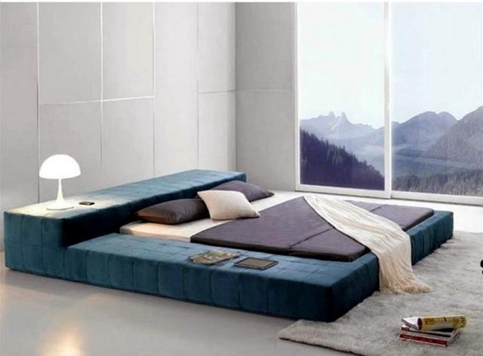 Огромная кровать с мягкой тканевой обивкой.