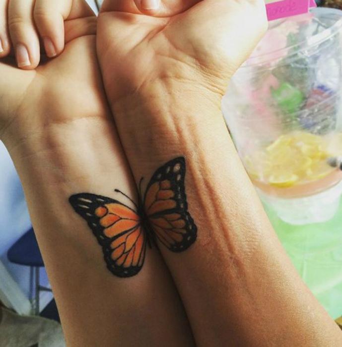 Изображение бабочек с одним крылом на запястьях матери и дочки.
