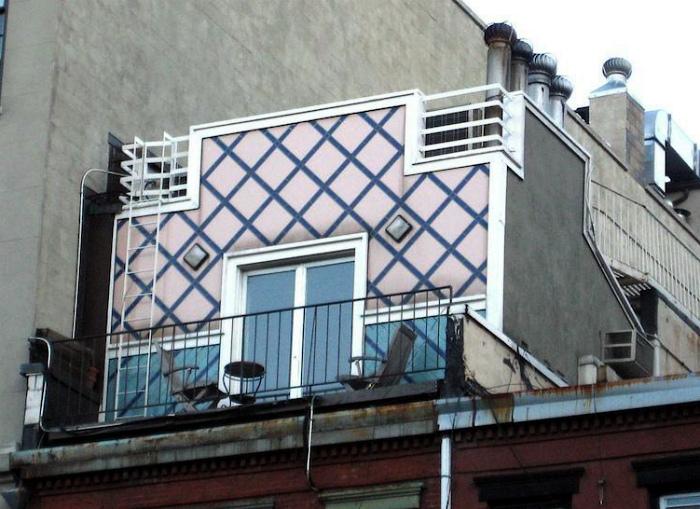 Небольшой розовый домик на крыше многоэтажки.