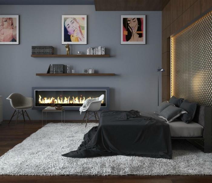 Темная спальня с яркими картинами и камином.